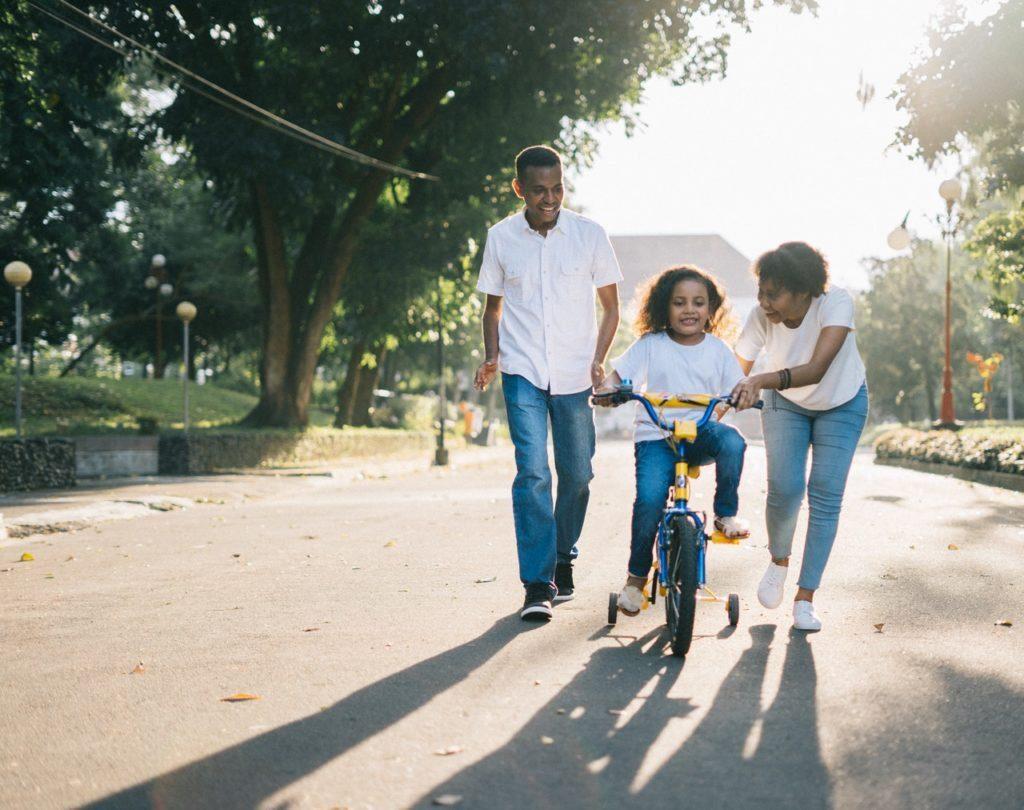 parents teaching a girl cycling