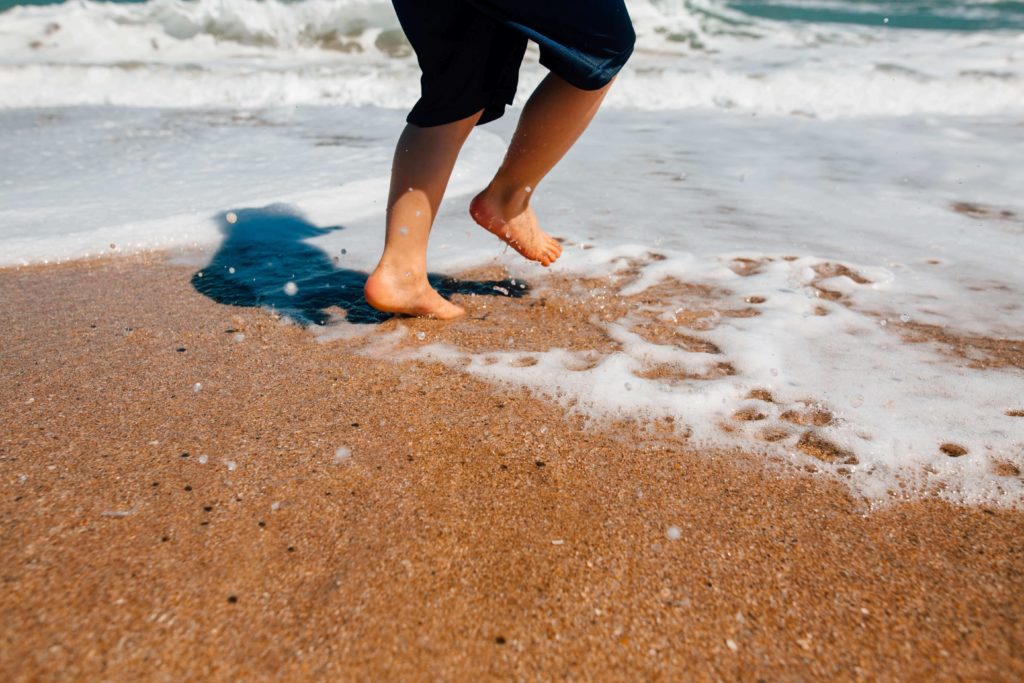 kid playing at the seaside with bare foot