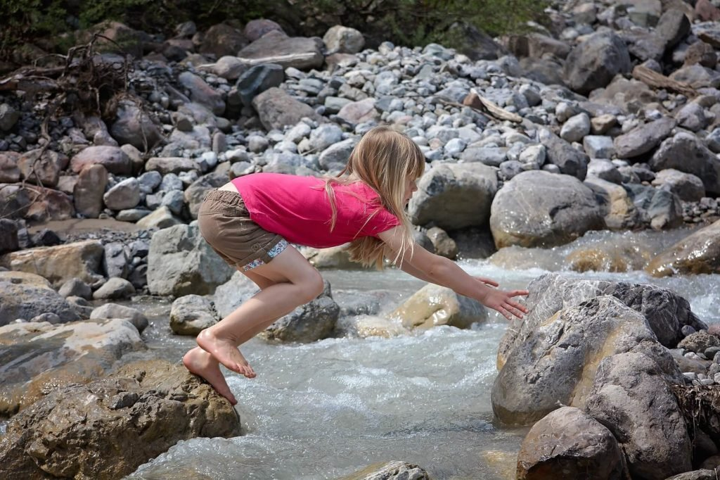 kid playing on the rock with bare foot
